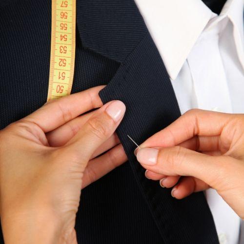 une femme plante un aiguille sur le revers d'un costume